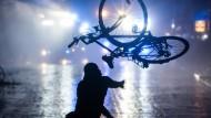 Ein Randalierer wirft ein Fahrrad in Richtung von Wasserwerfern.