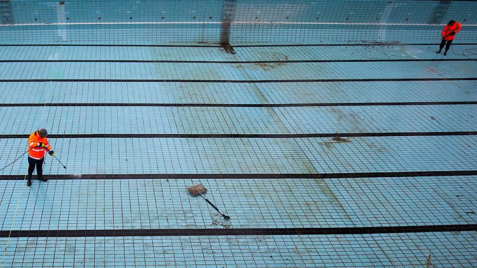 Zwei Bademeister reinigen das große Schwimmerbecken im Hamburger Kaifu-Bad mit Hochdruckreinigern. Ist die Schließung der Bäder eine Gefahr für die Gesellschaft?