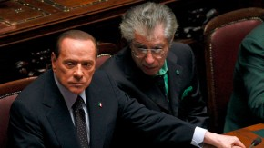 File photo of former Italian PM Berlusconi holding League North Party leader Bossi's hand in Rome
