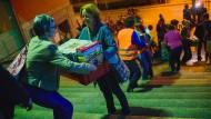 Freiwillige Helfer geben am 12.09.2015 in einer Schlange am Hauptbahnhof in München (Bayern) Hilfsgüter für Flüchtlinge weiter.