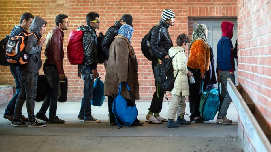 Flüchtlinge warten an einem Bahnhof in Brandenburg auf die Weiterfahrt mit Bussen
