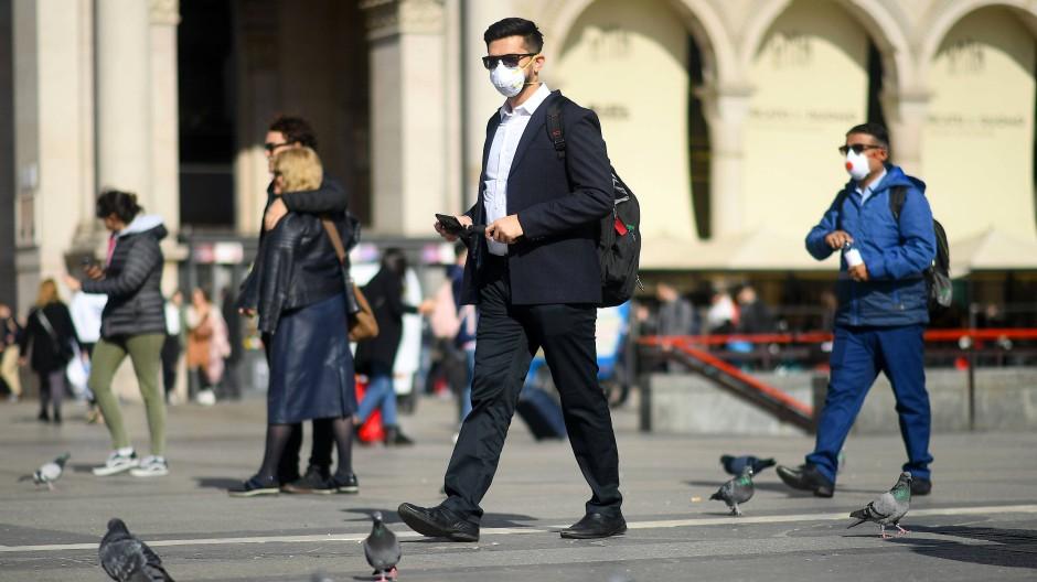 Zwei Männer in Mailand tragen Mundschutz.
