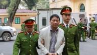 Der angeklagte Geschäftsmann Trinh Xuan Thanh (Mitte) wird von Polizisten zu einem Gericht gebracht.