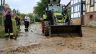 Nach Schlammlawinen: Helfer säubern in Homberg (Nordhessen) die Straße