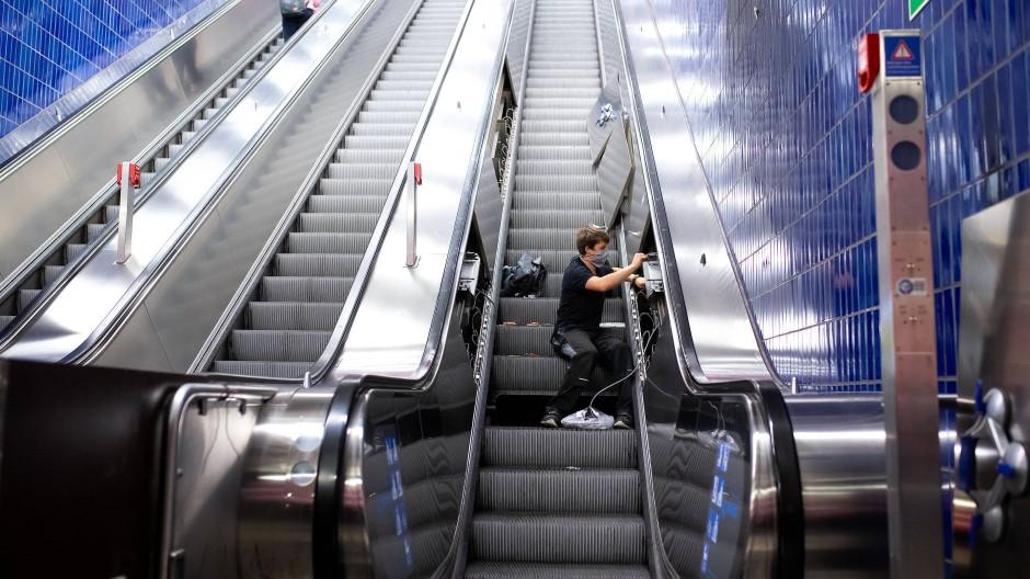 Ein Mitarbeiter von den Stadtwerken München, installiert an einer Rolltreppe im S- und U-Bahnhof Marienplatz UV-Lampen