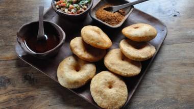 Vorspeise: Sopaipillas, dazu Öl mit fein gehackten Chilischoten (links), Pebre (Tomaten, Zwiebeln und Korianderblätter) und Merkén