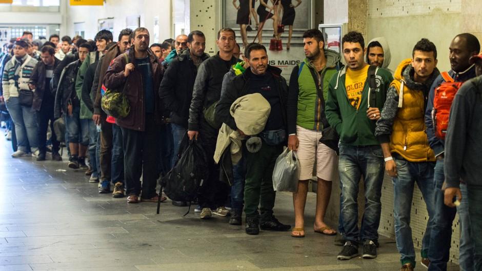 Flüchtlinge warten am Bahnhof in Schönefeld am Stadtrand von Berlin auf die Weiterfahrt mit dem Bus.