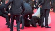 Mann schlüpft unter Kleid von Schauspielerin