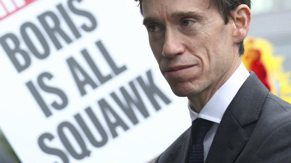 Der britische Entwicklungshilfeminister Rory Stewart vor einem gegen Boris Johnson gerichteten Plakat am Sonntag in London