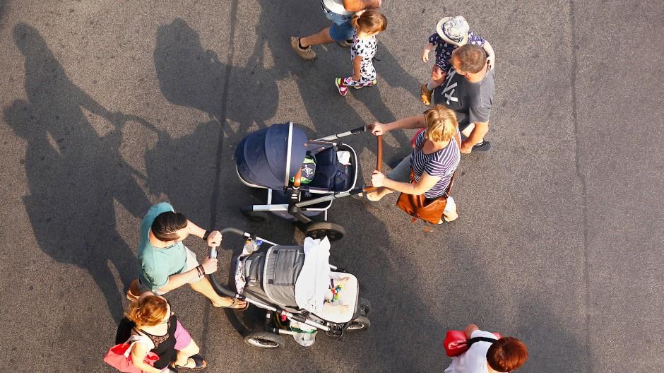 Zwei junge Familien mit Kindern begegnen sich, als sie über die Straße gehen. (Archiv)