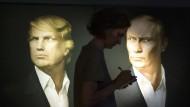 Seite an Seite: Eine Journalistin macht sich nach der amerikanischen Präsidentenwahl im Moskauer Union-Jack-Pub vor den Porträts von Trump und Putin Notizen.