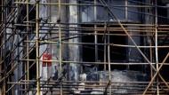 Ein Fanal der Sinnlosigkeit: Feuerlöscher am Gerüst des ausgebrannten Hochhauses