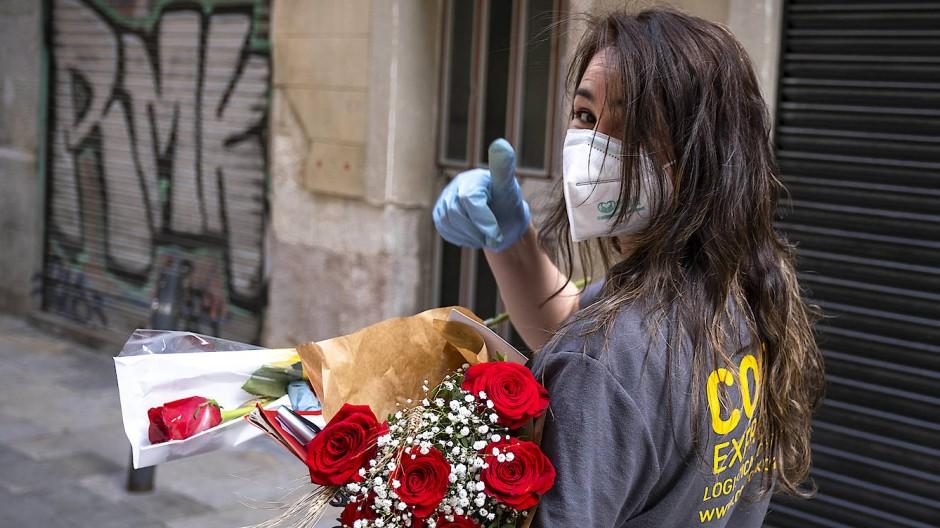 Zeigen, dass man füreinander da ist, kann man auch mit Abstand oder Maske: Blumenbotin in Barcelona im April.