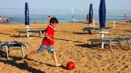 Irgendwann am Abend ist der Sand endlich kühl genug, um barfuß Fußball spielen zu können: Das Kind liebt den Strand, die Eltern das Städtchen.