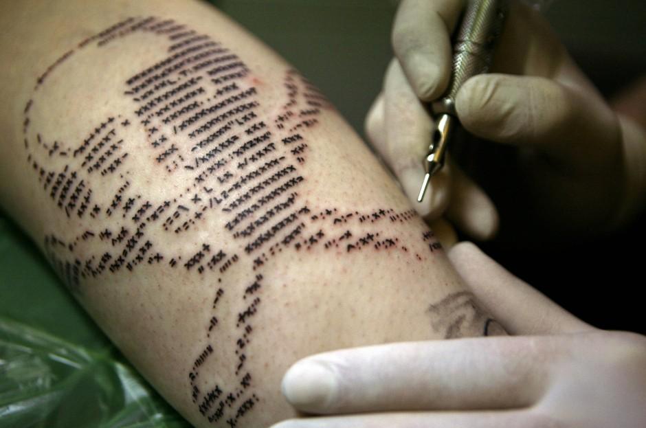 Nach digitaler Vorlage: Ein Tätowierer sticht ein Totenkopf-Motiv, bestehend aus Zeichen des Computercodes ASCII (American Standard Code for Information Interchange).