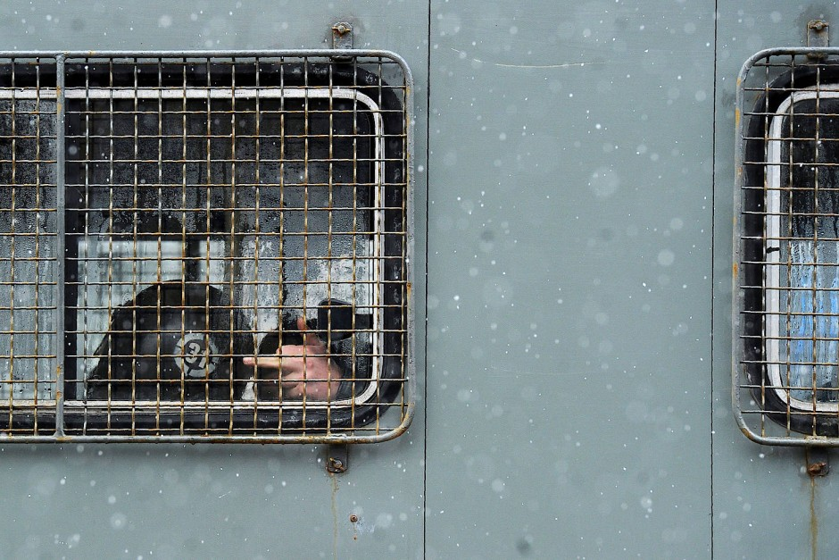 Ein Polizist zeigt den Demonstranten aus dem Einsatzwagen heraus, was er von ihnen hält.