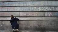 Menschen schreiben Botschaften an eine Hauswand in Brüssel, als Zeichen für die Getöteten und Verletzten.