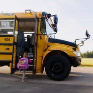 Ein kleines Mädchen steigt in den Schulbus.