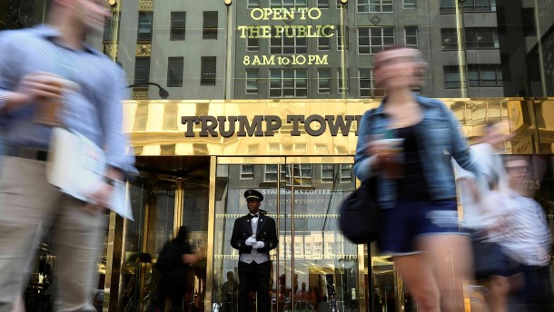 A doorman stands as people walk past the Trump Tower in New York