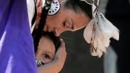 Eine Frau mit Federschmuck umarmt ihr Kind bei einer Gedenkveranstaltung in Toronto am 6. Juni