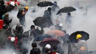 Demonstranten versuchen sich vor dem Tränengas der Polizei zu schützen.