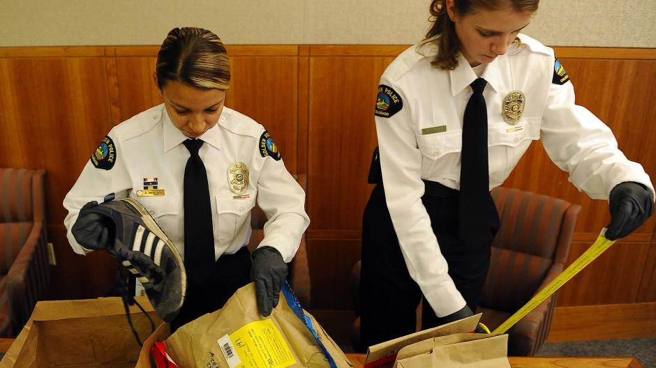Beweismittel: Zwei Polizistinnen zeigen Schuhe und Handschuhe, die 2011 bei der Durchsuchung der Wohnung des Serientäters sichergestellt wurden.