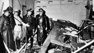 """Reichsmarschall Hermann Göring (helle Uniform) und der Chef der """"Kanzlei des Führers"""", Martin Bormann (links), begutachten die Zerstörung im Raum der Karten-Baracke im Führerhauptquartier Rastenburg, wo Oberst Stauffenberg am 20. Juli 1944 eine Sprengladung zündete, mit der Absicht Hitler zu töten"""