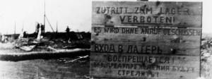 """""""Zutritt zum Lager verboten! Es wird ohne Anruf geschossen"""", steht auf einem Warnschild am Lager Malyj Trostenez im Juli 1944."""