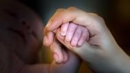 Ein Recht auf ein eigenes Kind gibt es nicht: Eine Mutter hält die Hand ihres Neugeborenen.