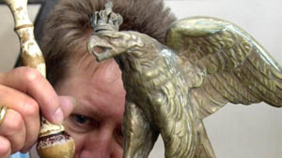 Mit einem Pinsel säubert eine Museums-Mitarbeiterin einen preussischen Gardehelm