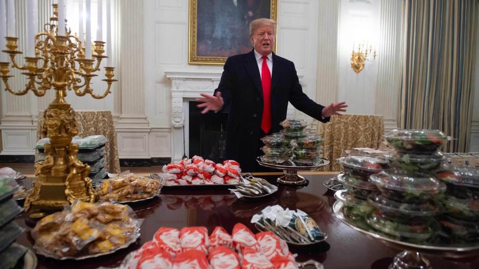 Trump und viele Künstler verbindet, dass sie oft als Parvenüs und stillose Emporkömmlinge bezeichnet wurden: Der einstige Präsident 2018 mit Fast Food bei einer Zeremonie zu Ehren der Gewinner der College Football Playoffs im Weißen Haus.