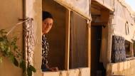 Die Syrerin Laila Huria schaut in einem Flüchtlingslager in dem libanesischen Ort Arsal aus dem Fenster. Kurz nach der Aufnahme wollten sie und ihre Familie nach Syrien zurückkehren.