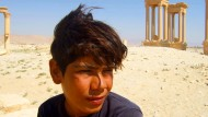 """Der Andenkenverkäufer Mohamad vor den Ruinen, die sein Arbeitsplatz waren: Szene des Dokumentarfilms """"Palmyra"""""""