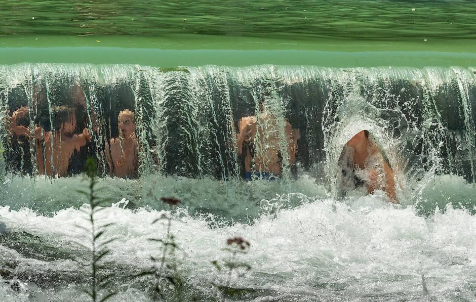 Kinder unter einem kleinen Wasserfall am Eisbach