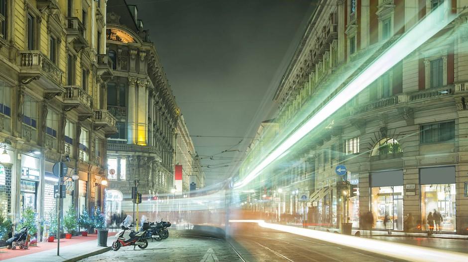 Nächtliche Langzeitbelichtung aus Mailand. Die Lichter der Straßenbahn zeichnen Linien auf den Film.