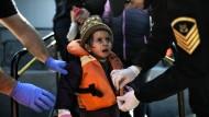 Die Küstenwache nimmt einem kleinen Mädchen auf Lesbos nach der Überfahrt die Schwimmweste ab.