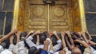 Sie waren nicht die ersten, die hier ihren Gott verehrten: gläubige Muslime vor der Goldenen Tür der Kaaba in Mekka