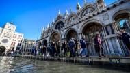 Mitte November in Venedig: Touristen gehen über Stege vor dem Markusdom.