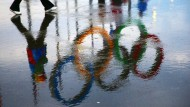 Nichts als ein Trugbild: Die Olympischen Ringe im Spiegel einer Pfütze im Olympiapark