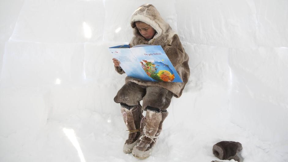 Greta kennt er vermutlich auch schon: Ein junger Inuit in der Arktis liest ein Buch über die Zukunft der sich erwärmenden erde.