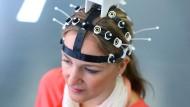 Ulrike Baum trägt in Magdeburg im Zentrum für Neurowissenschaftliche Innovation und Technologie (ZENIT) ein drahtloses EEG-Headset.
