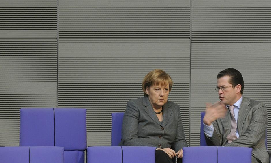 Die Maskentänzerin und der Filmstar: Angela Merkel mit Karl-Theodor zu Guttenberg im Bundestag