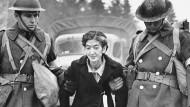 Minderheiten als Feindbild: Eine japanischstämmige Amerikanerin, wohnhaft auf Bainbridge Island im Bundesstaat Washington, wird am 30. März 1942 von Sanitätssoldaten zum Transport in eines der inländischen Internierungslager abgeführt.