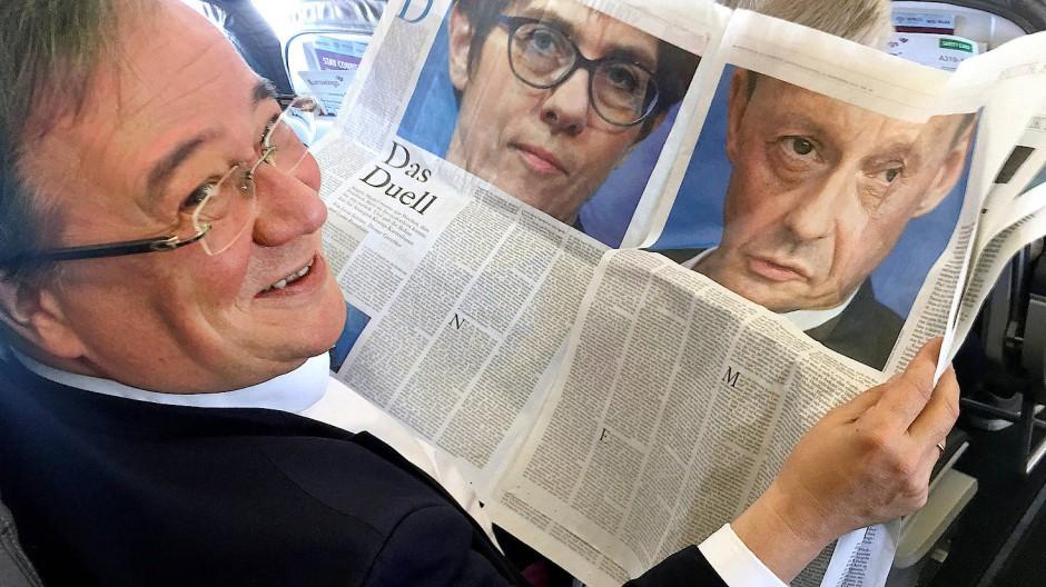 Armin Laschet betrachtet seine Konkurrenz in der Zeitung.