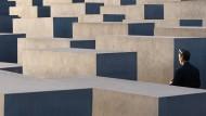 Das Denkmal für die ermordeten Juden Europas in Berlin im Abendlicht. Viele Besucher verhalten sich dort unangemessen, turnen, springen und biken zwischen den Stelen.