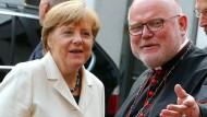 Der Herrgott, sagt Kardinal Marx, habe uns die Aufgabe auf den Tisch gelegt: Bundeskanzlerin Angela Merkel beruft sich auf den Kirchenmann.