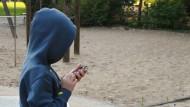 Mit dem Smartphone auf dem Spielplatz. Was wissen die Eltern des Jungen von diesem Moment?