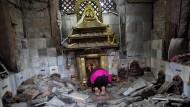 Eine Frau betet in einem zerstörten Tempel: Nicht nur die Menschen, auch die Götter sind durch das Erdbeben obdachlos geworden.