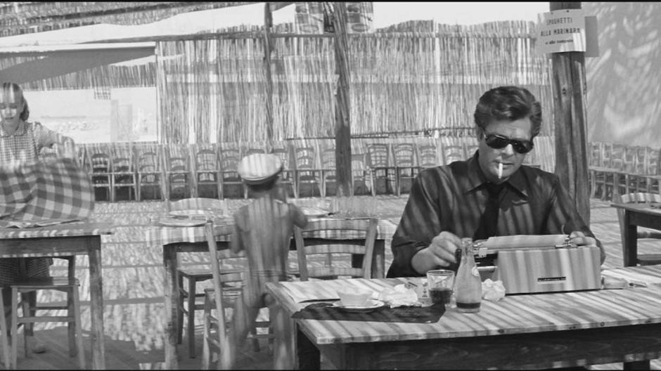 Marcello sitzt schreibend in einer Trattoria, im Hintergrund deckt eine junge Bedienung im Lichtkreidegestrichel unterm Strohdach ein: Szene aus La dolce vita (1960).