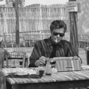 """Marcello sitzt schreibend in einer Trattoria, im Hintergrund deckt eine junge Bedienung im Lichtkreidegestrichel unterm Strohdach ein: Szene aus """"La dolce vita"""" (1960)."""
